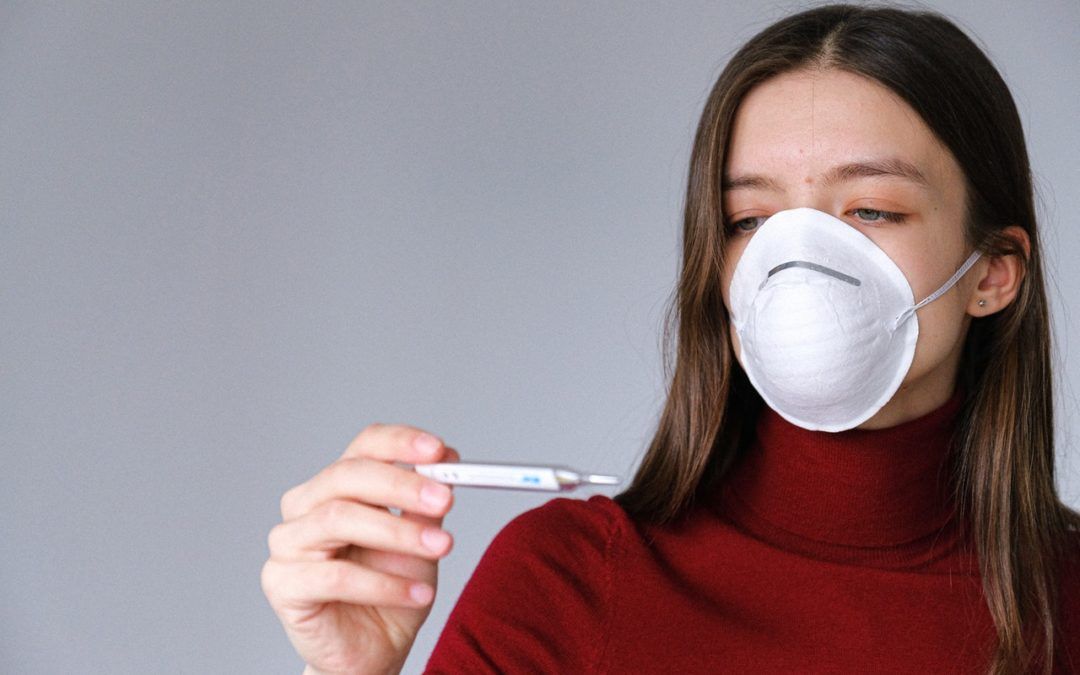 Woman in face mask checking her temperature